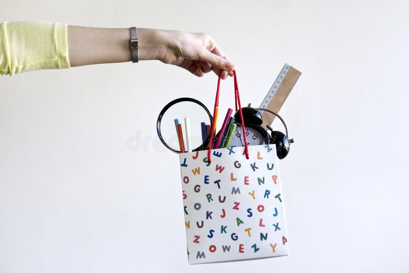 Mão fêmea que guarda o saco de compras do papel com fontes de escola fotos de stock