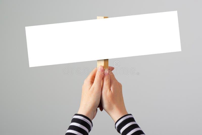 Mão fêmea que guarda o sinal vazio da bandeira do modelo como o espaço da cópia foto de stock royalty free