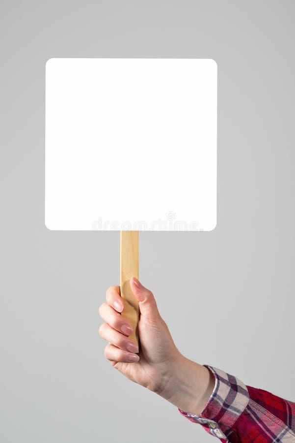 Mão fêmea que guarda o sinal vazio da bandeira do modelo como o espaço da cópia fotografia de stock royalty free