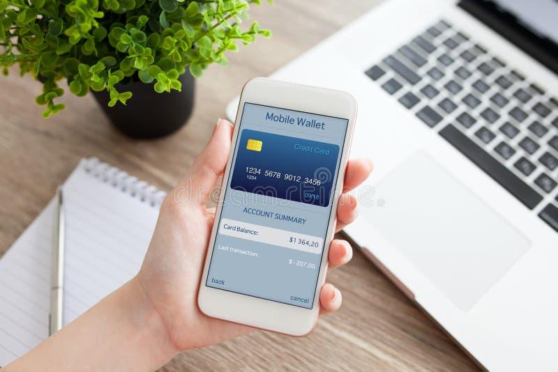Mão fêmea que guarda o telefone com a carteira móvel do app na tela fotografia de stock royalty free