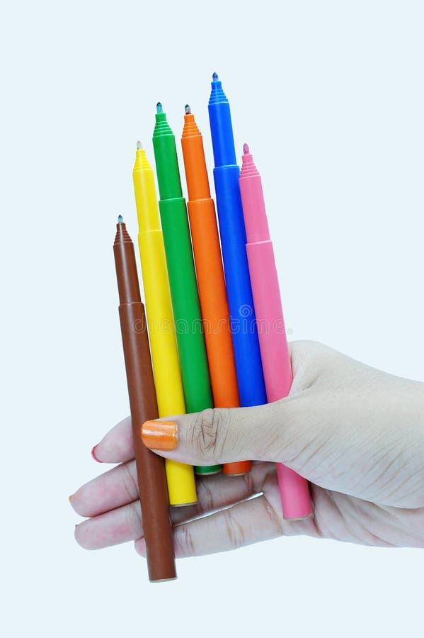 Mão fêmea que guarda os marcadores da cor, azul, amarelo, verde, cor-de-rosa, laranja, marrom fotografia de stock