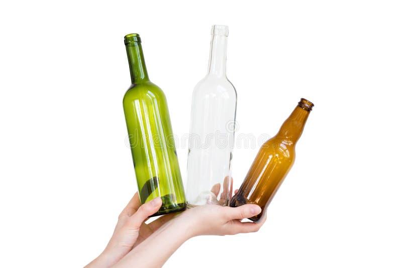 Mão fêmea que guarda tipos diferentes das garrafas de vidro isoladas no branco Desperdício reciclável Reciclando, reutilização, t fotografia de stock royalty free