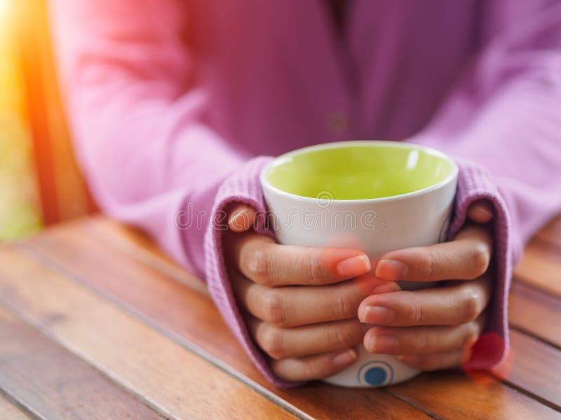 Mão fêmea que guarda um copo na tabela de madeira fotografia de stock