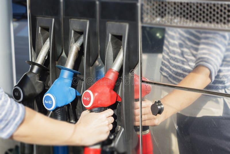 Mão fêmea que guarda uma arma do reabastecimento Carros de enchimento com gasolina foto de stock