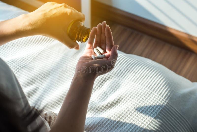 Mão fêmea que guarda uma medicina, mãos da mulher com os comprimidos em derramar comprimidos fora da garrafa imagem de stock