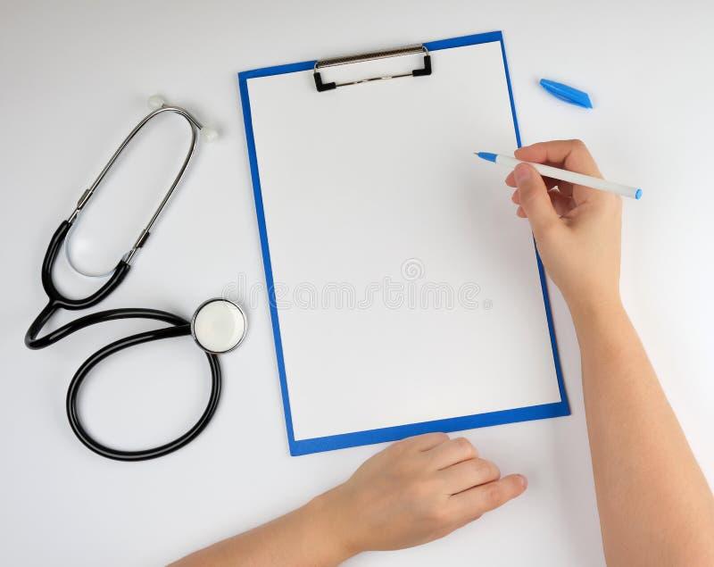 mão fêmea que guarda uma pena para escrever um diagnóstico ou uma prescrição imagem de stock