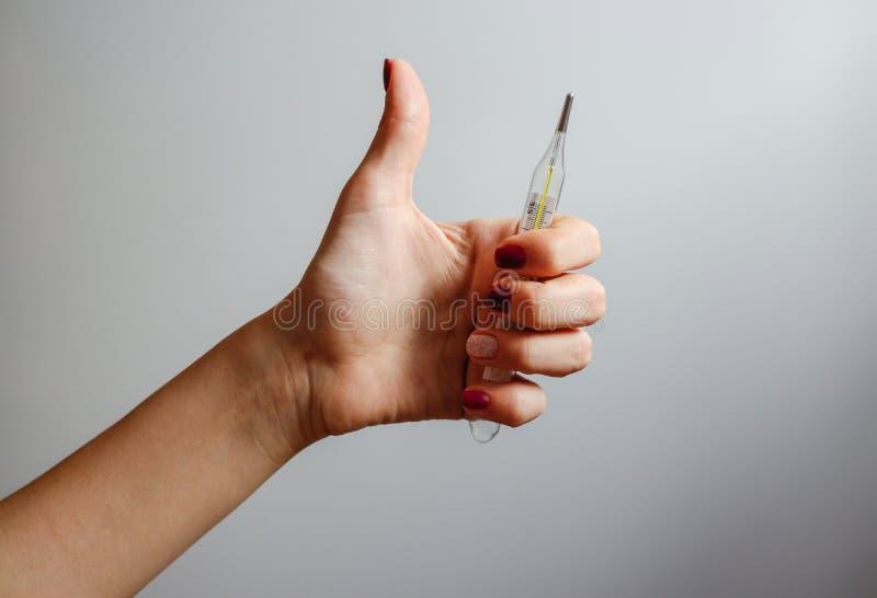 A mão fêmea que guardam um termômetro de mercúrio e as mostras manuseiam acima fotos de stock
