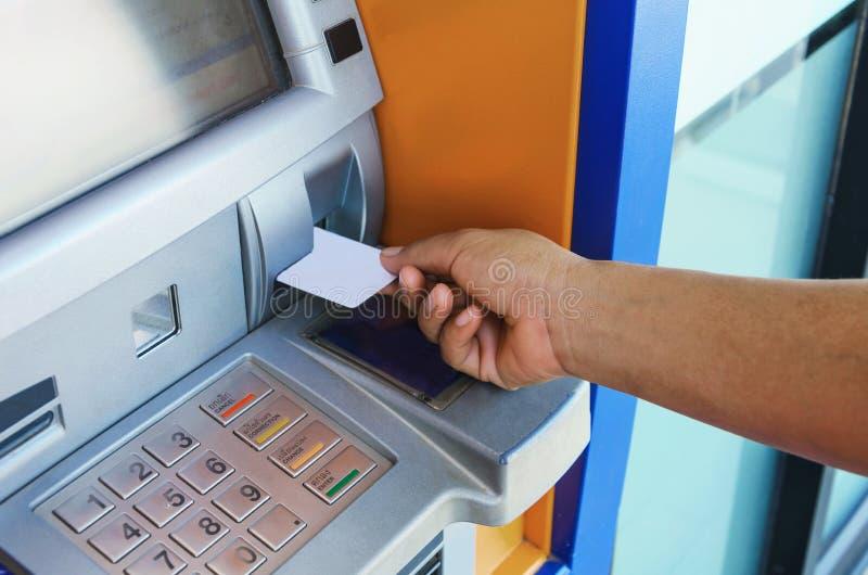 Mão fêmea que introduz o cartão de ATM na máquina do banco do ATM imagem de stock