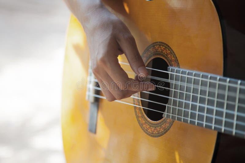 Mão fêmea que joga uma guitarra acústica imagens de stock royalty free