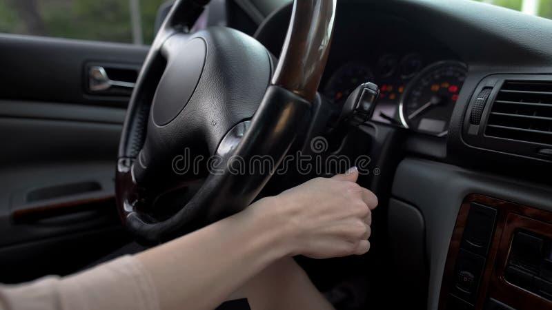 Mão fêmea que liga o motor de automóveis, mulher de negócio que conduz o veículo luxuoso, fim acima imagens de stock