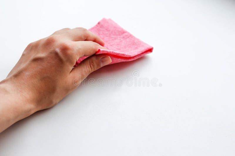 Mão fêmea que limpa o pano do rosa da poeira Limpeza molhada closeup Mim fotografia de stock royalty free