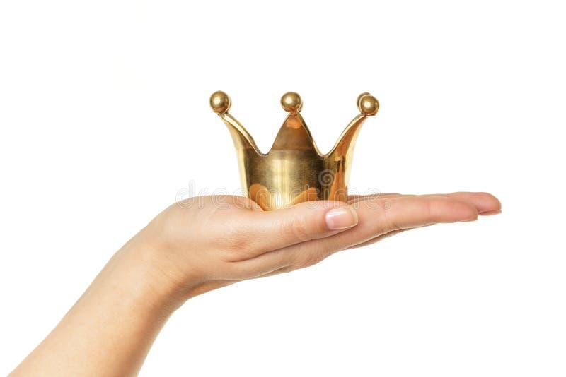 Mão fêmea que mantém a coroa dourada isolada no fundo branco imagem de stock