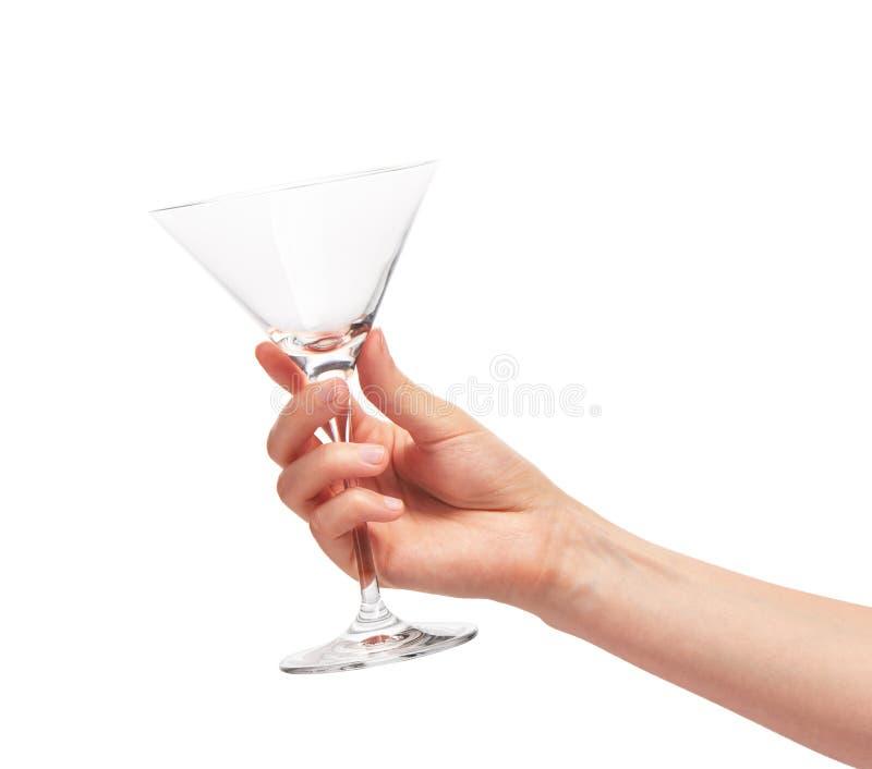 Mão fêmea que mantém martini limpo vazio de vidro contra o branco imagens de stock
