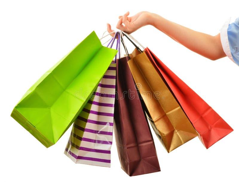 Mão fêmea que mantém os sacos de compras de papel isolados no branco imagens de stock royalty free