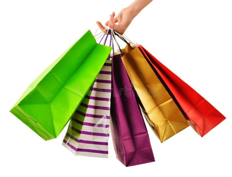 Mão fêmea que mantém os sacos de compras de papel isolados no branco fotografia de stock royalty free