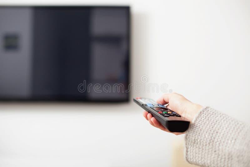 Mão fêmea que mantém a tevê de controle remoto fotos de stock royalty free