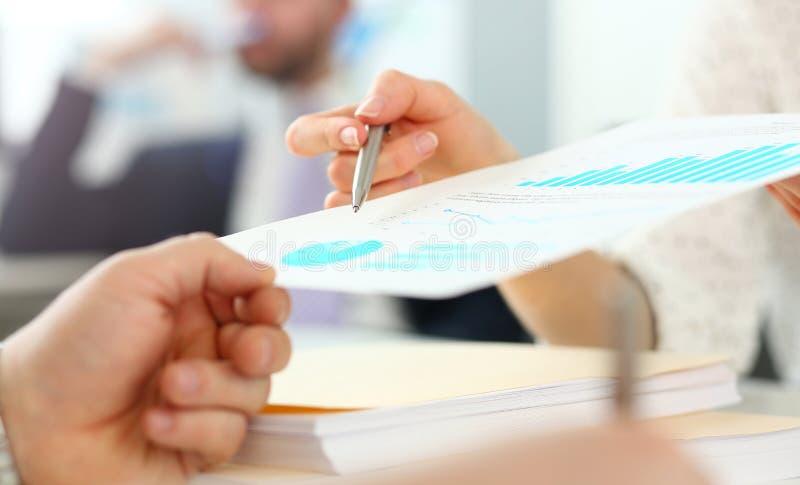Mão fêmea que mostra o papel financeiro do relatório ao cliente imagem de stock