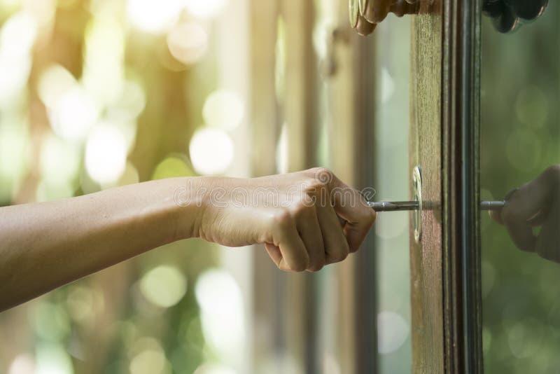 Mão fêmea que põe a chave da casa na porta da rua fotografia de stock