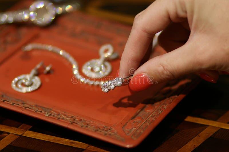 Mão fêmea que pegara a caixa de joia japonesa do formulário do anel de diamante foto de stock royalty free