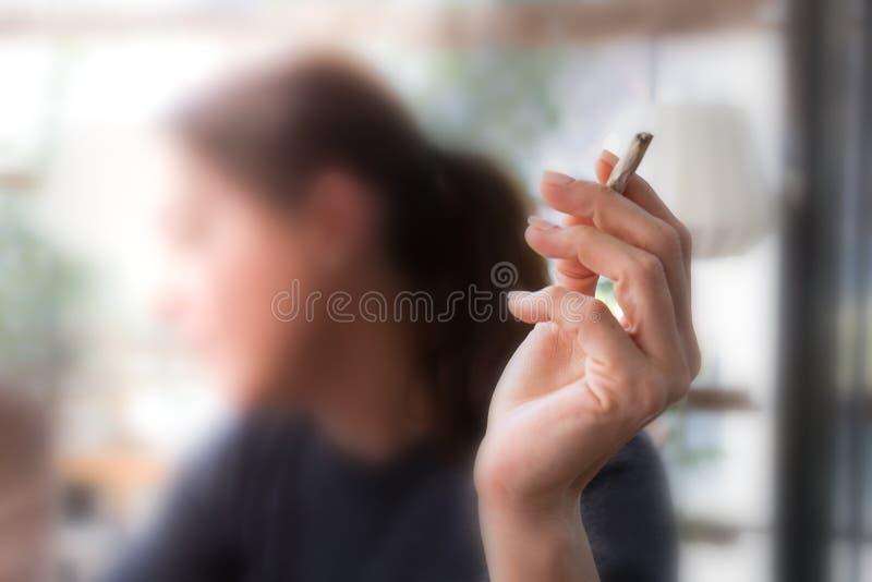Mão fêmea que prende um cigarro foto de stock