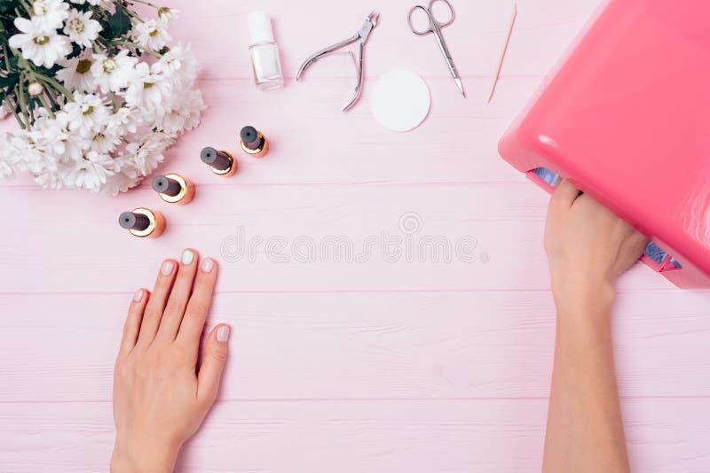 Mão fêmea que seca a laca da goma-laca na lâmpada ultravioleta fotografia de stock