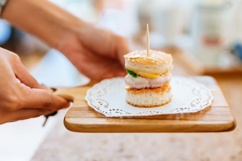 Mão fêmea que serve Mini Chicken Burger na placa de desbastamento de madeira com fundo do borrão fotos de stock royalty free