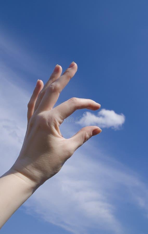 Mão fêmea que trava uma nuvem foto de stock royalty free