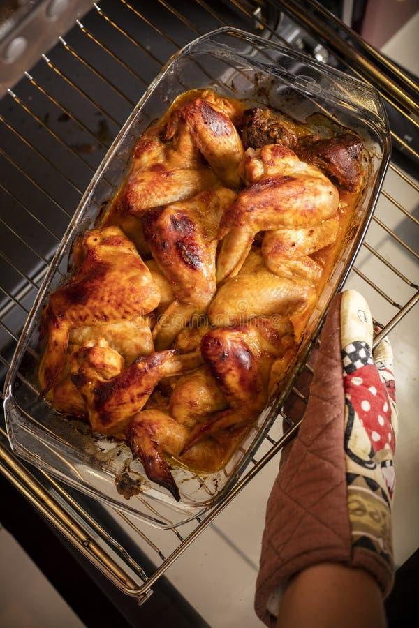 A mão fêmea retira as asas de galinha do forno foto de stock royalty free