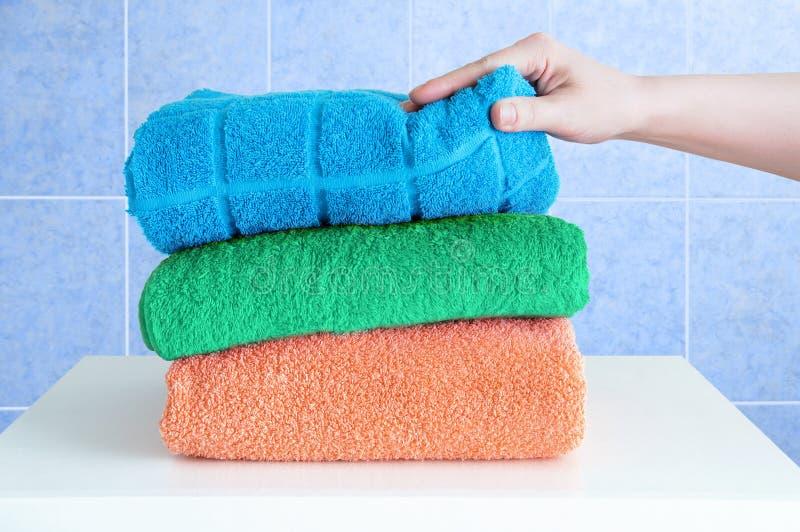 A mão fêmea toma toalhas de terry em uma tabela de cabeceira branca no banheiro fotografia de stock royalty free