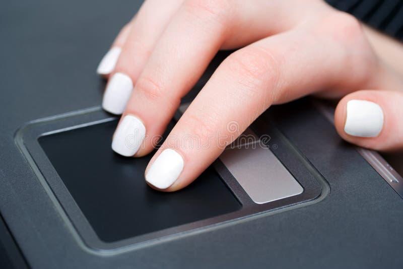 Mão fêmea usando o touchpad. fotografia de stock