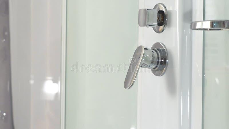 Mão fêmea usando a torneira do banheiro na cabine do chuveiro Close up de um regulador do botão do chuveiro e de seu distribuidor fotografia de stock