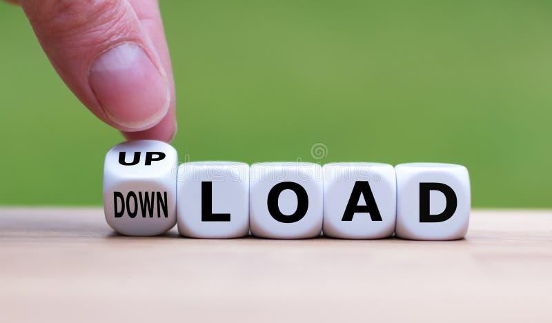 A mão faz um dado e muda a palavra 'upload' para 'download' imagens de stock royalty free