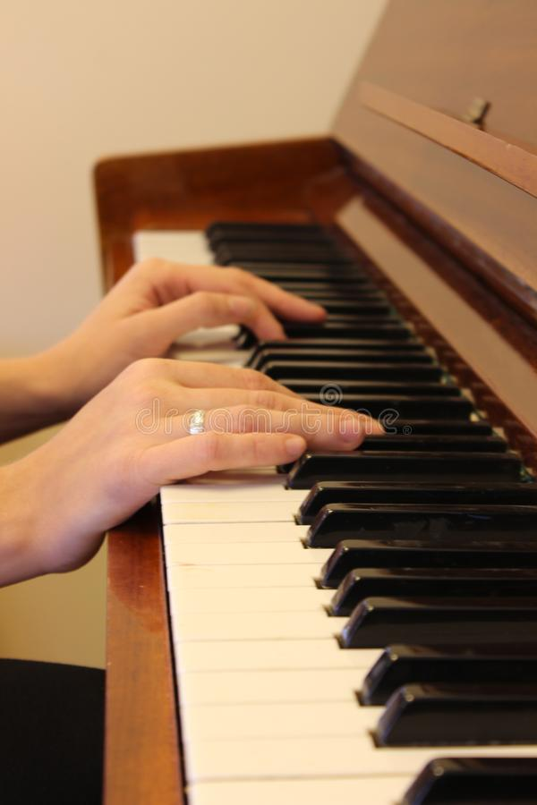 Mão feliz do ` s da mulher que joga o piano na manhã imagens de stock