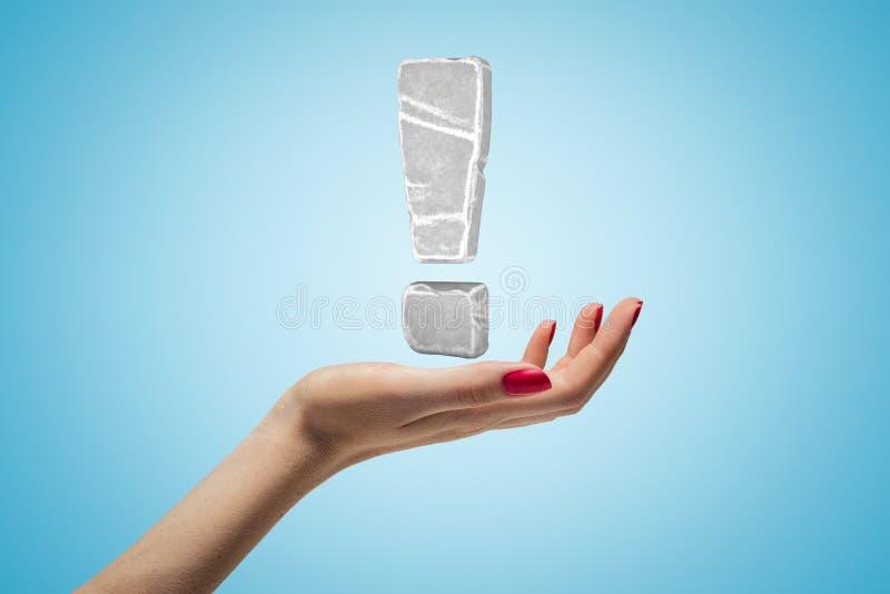 Mão feminina com ponto de exclamação de concreto cinzento sobre fundo azul imagem de stock royalty free