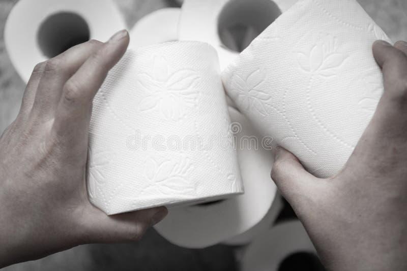 Mão feminina pega um rolo de papel higiênico Problema gastrointestinal, diarreia conceito foto de stock