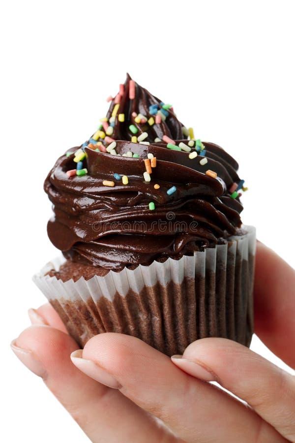 Mão feminino bonita que guarda o cupca apetitoso saboroso do chocolate fotos de stock