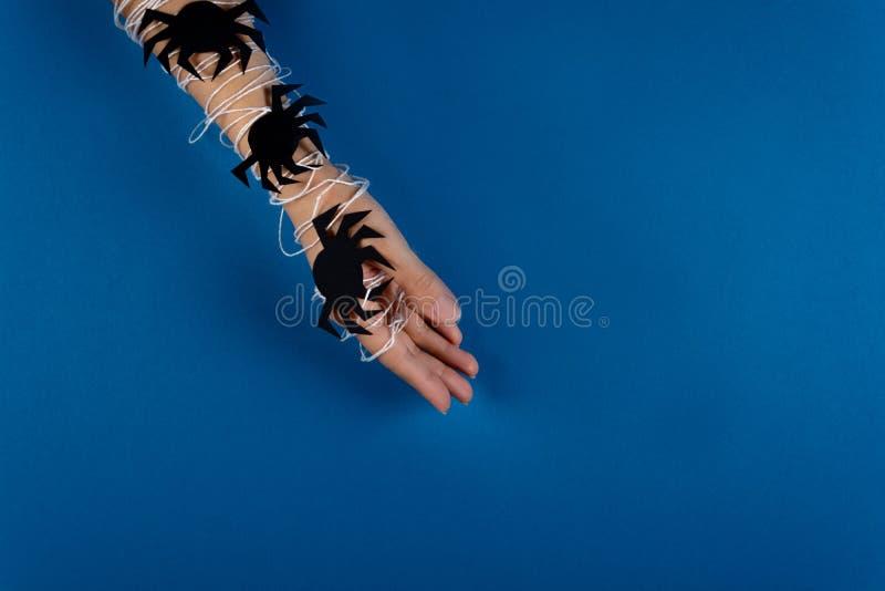 Mão feminino envolvida na Web branca com as aranhas de papel pretas no fundo azul Conceito de Halloween foto de stock