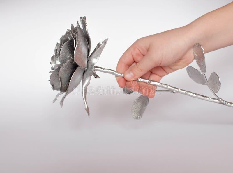A mão forjada aumentou Feito a mão de Rosa forjado do metal em uma parte traseira branca imagem de stock