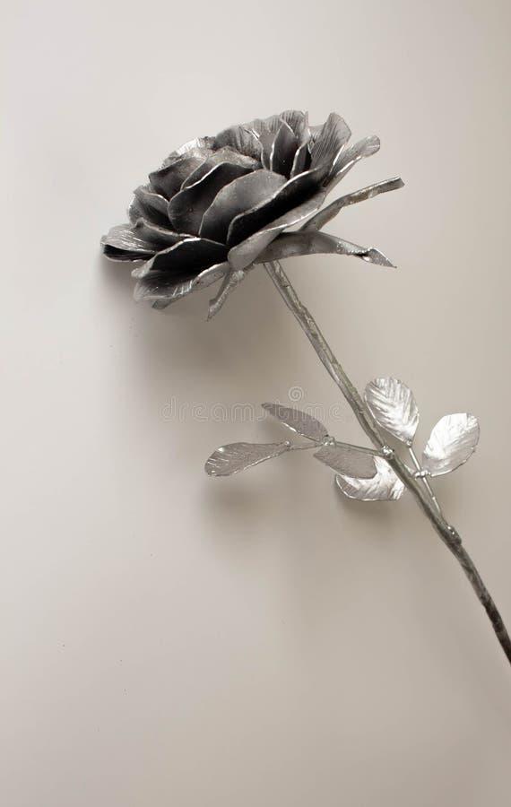 A mão forjada aumentou Feito a mão de Rosa forjado do metal em uma parte traseira branca foto de stock royalty free