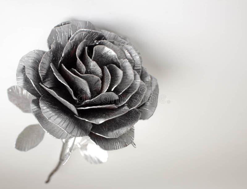 A mão forjada aumentou Feito a mão de Rosa forjado do metal em uma parte traseira branca foto de stock