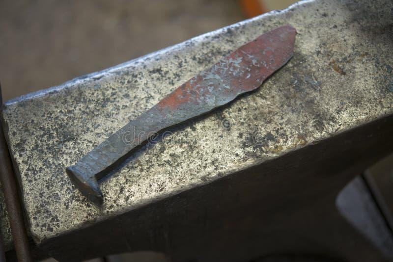 A mão forjou a faca de aço no batente foto de stock