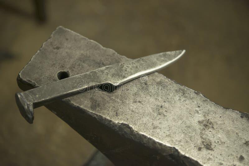 A mão forjou a faca de aço no batente fotografia de stock royalty free
