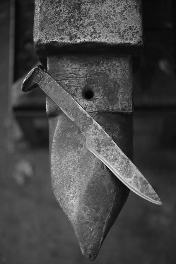 A mão forjou a faca de aço no batente foto de stock royalty free
