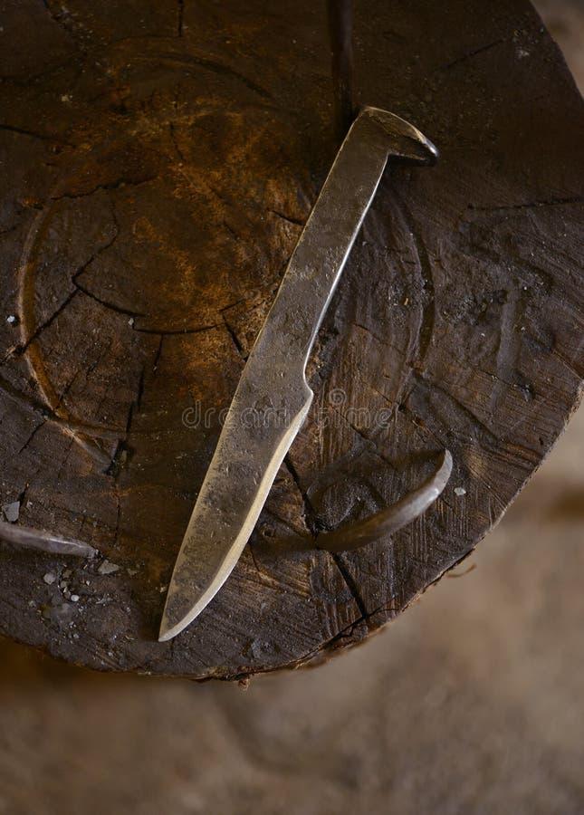 A mão forjou a faca de aço no batente fotografia de stock