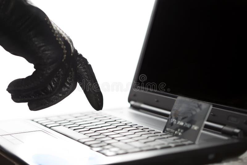 Mão gloved dos hacker no trabalho em um portátil imagens de stock