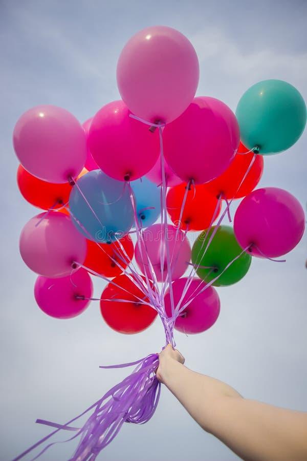 A mão guarda balões no céu imagem de stock royalty free
