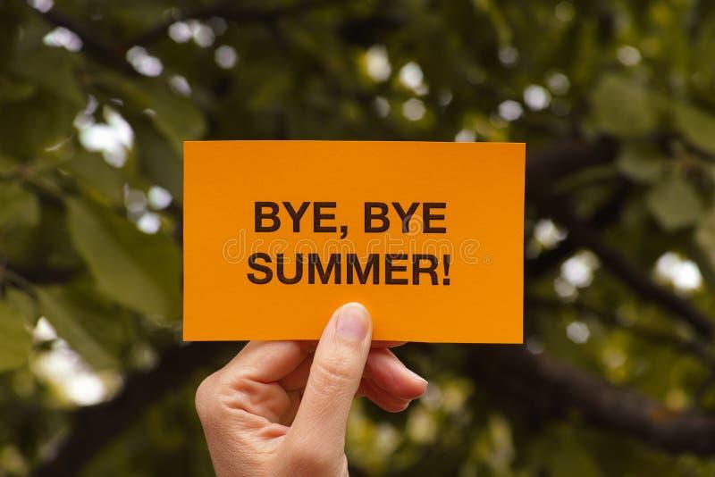 A mão guarda o pedaço de papel amarelo que diz o adeus, verão do adeus! fotos de stock royalty free