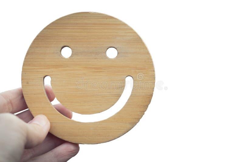 A mão guarda o sorriso redondo de madeira no fundo isolado branco Mão que guarda a cara de sorriso nenhum corpo Emoji, a emoção d imagem de stock