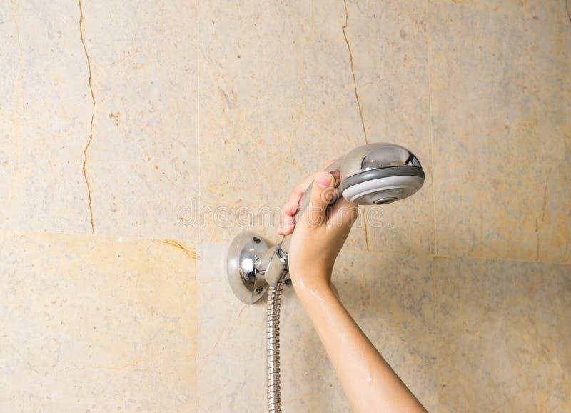 A mão guarda um chuveiro no fundo dos mármores fotos de stock royalty free