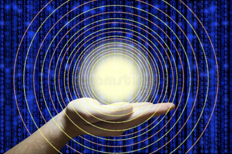 A mão guarda uma bola de incandescência que emite-se círculos dos dados imagem de stock royalty free